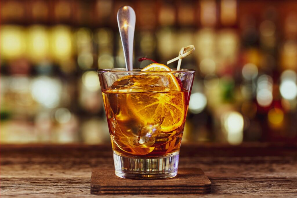American cocktail is old-fashioned. Cocktail stands on a wooden bar in a nightclub