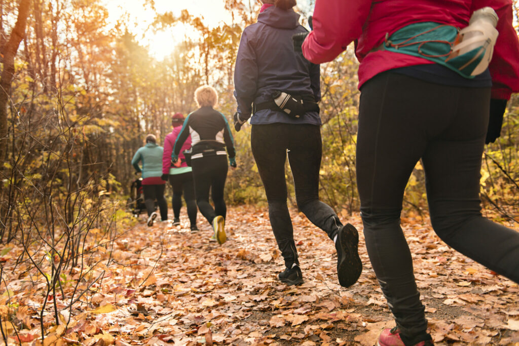 A woman group out running together in an autumn park they run a race or train in a healthy outdoors lifestyle concept